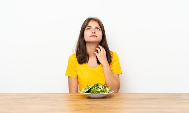 Menina caucasiana com salada pensando uma idéia Foto Premium