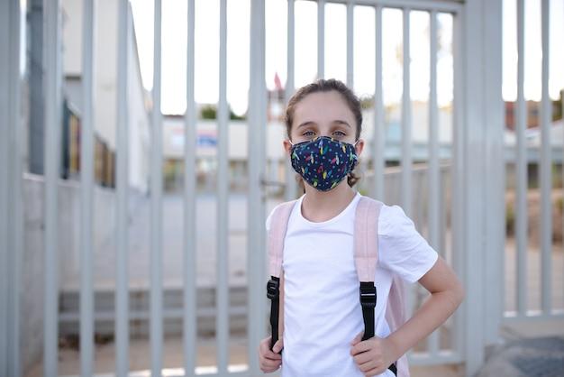 Menina caucasiana de olhos azuis esperando para entrar na escola no novo normal com uma máscara Foto Premium