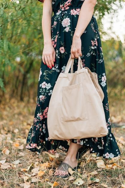 Menina caucasiana detém comprador de linho no pôr do sol ao ar livre Foto Premium