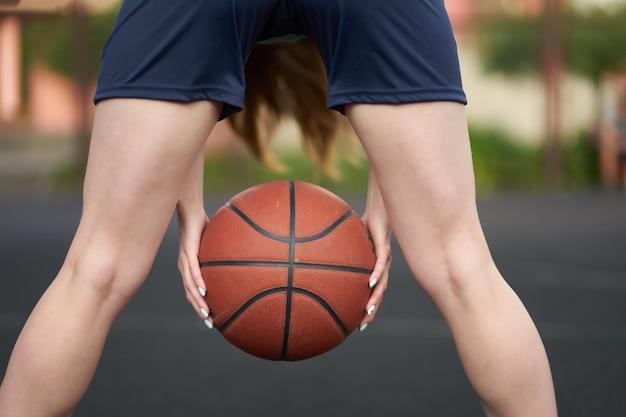 Menina caucasiana, segurando uma bola entre as pernas durante um jogo de basquete de rua na quadra ao ar livre Foto Premium