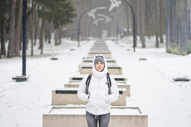 Menina caucasiana, vestida de jaqueta branca, desfrutando de neve no parque Foto Premium