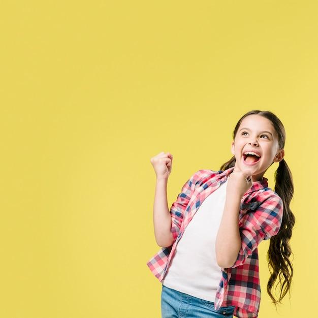 Menina, celebrando, ganhar, em, estúdio Foto gratuita