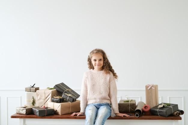 Menina cercada por caixas de presente Foto gratuita