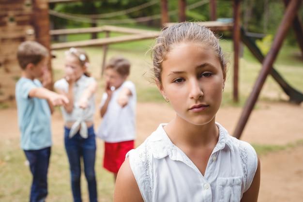 Menina chateada com amigos fofocando no fundo Foto Premium