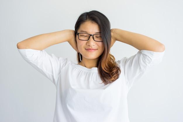 Menina chinesa despreocupada satisfeita que cobre as orelhas com as mãos. Foto gratuita