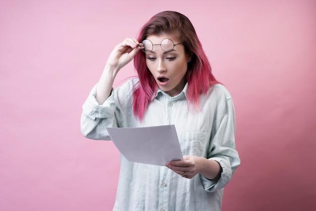 Menina chocada com óculos e papel Foto gratuita