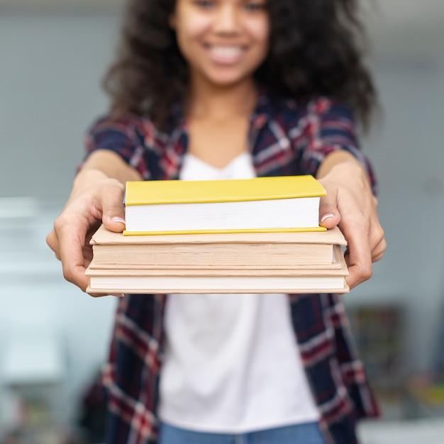 Menina close-up, segurando, pilha livros Foto gratuita