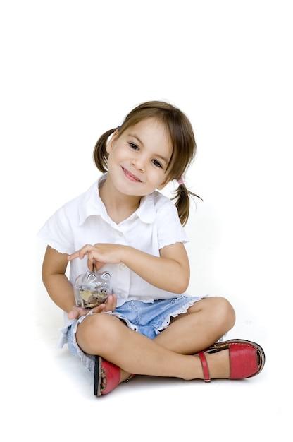 Menina colocando dinheiro no cofrinho isolado Foto Premium