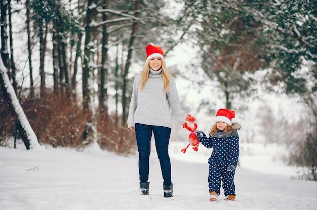 Menina com a mãe brincando em um parque de inverno Foto gratuita