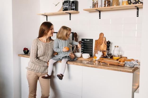 Menina com a mãe na cozinha em casa. Foto Premium