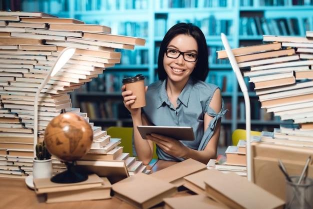 Menina com a tabela cercada por livros na biblioteca na noite. Foto Premium