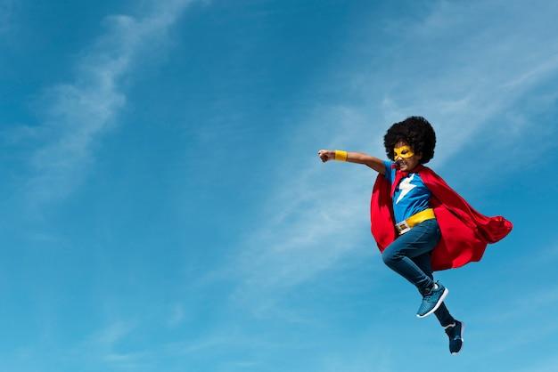Menina, com, afro, jogando superhero Foto gratuita