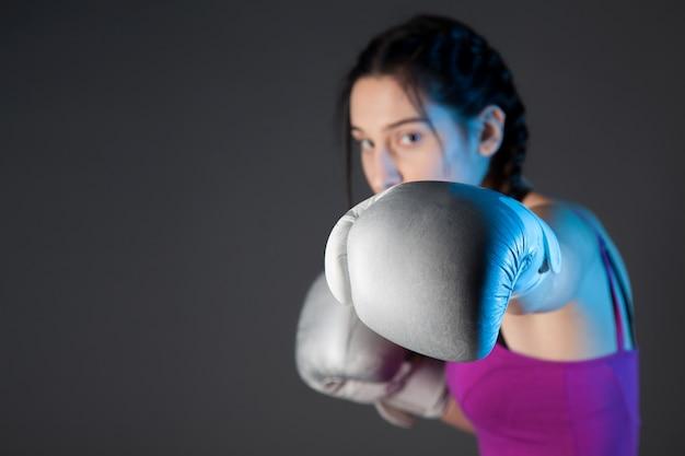 Menina com as luvas de boxe prata, fundo preto com espaço de cópia Foto Premium