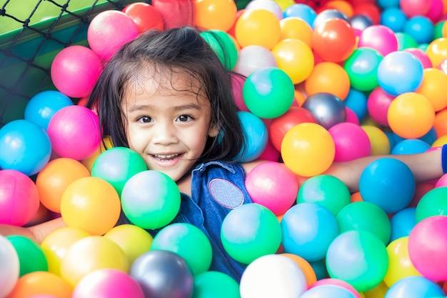 Menina com bolas de plástico coloridas. criança engraçada se divertindo dentro de casa. Foto Premium