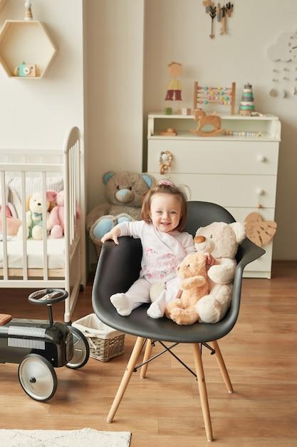 Menina com brinquedos no quarto das crianças Foto Premium