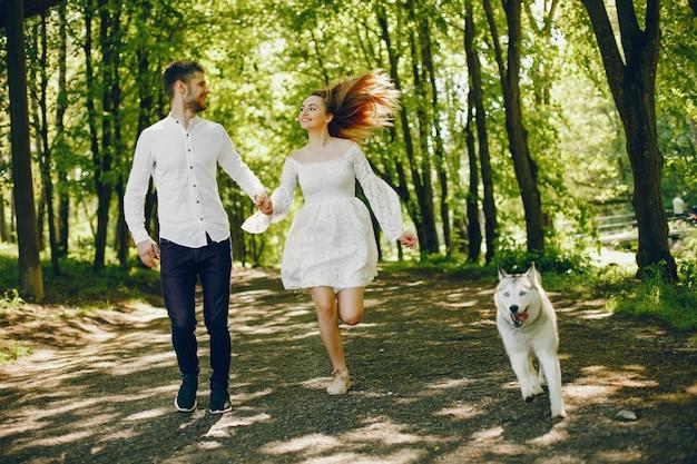 Menina com cabelo claro vestido de branco está jogando junto com seu cachorro e namorado Foto gratuita