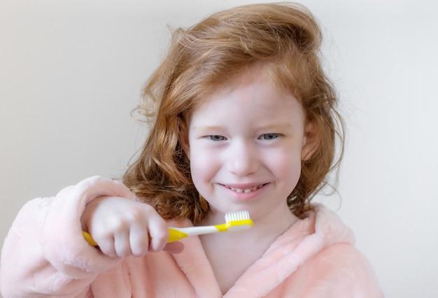 Menina com cabelo ruivo, escovar os dentes, escova de dentes amarela, higiene dental, manhã noite conceito saudável estilo de vida Foto Premium