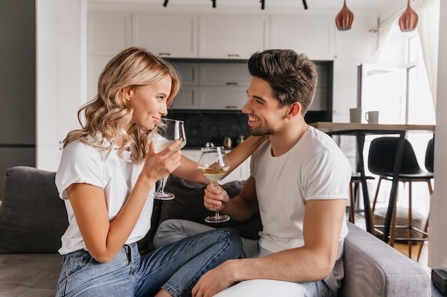 Menina com cabelos ondulados, olhando para o namorado enquanto bebia vinho. retrato interior de casal romântico, aproveitando o encontro. Foto gratuita