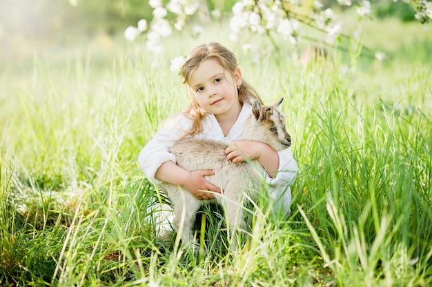 Menina com cabra de bebê. amizade de criança e animais. infância feliz. Foto Premium