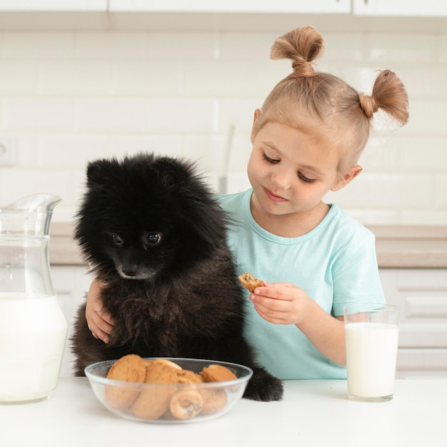 Menina com cachorro bebendo leite Foto gratuita