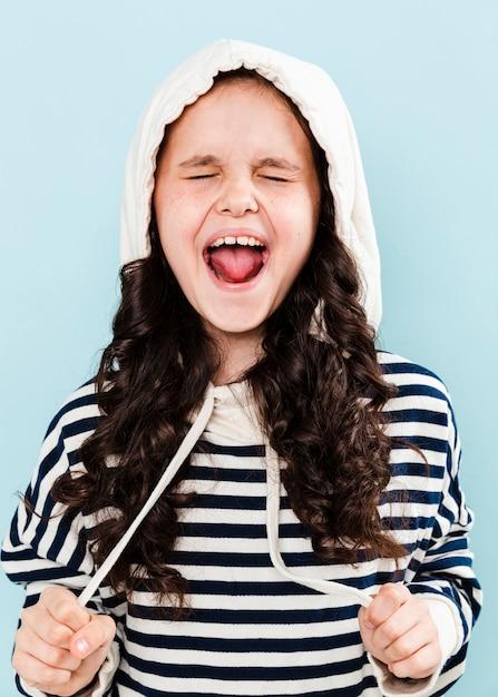 Menina com capuz fazendo caretas Foto gratuita