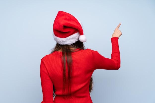 Menina com chapéu de natal isolado azul apontando para trás com o dedo indicador Foto Premium