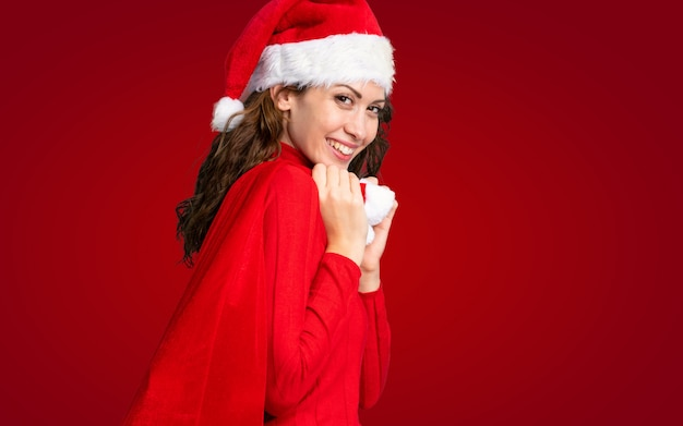 Menina com chapéu de natal segurando uma sacola cheia de presentes sobre parede vermelha isolada Foto Premium