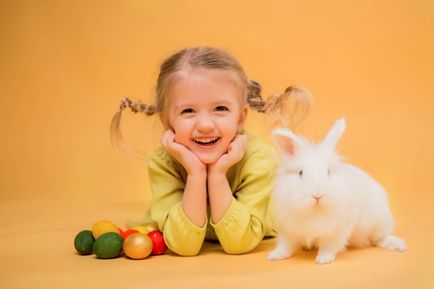 Menina com coelhinho da páscoa em fundo amarelo Foto Premium