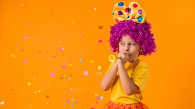 Menina com confete e fantasia de palhaço Foto gratuita