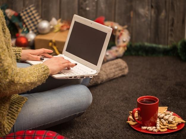 Menina com decoração de natal de computador Foto gratuita