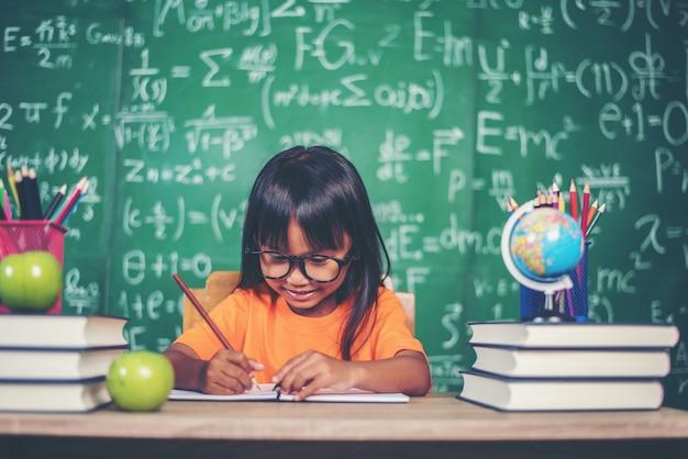 Menina com desenho a lápis na aula na sala de aula Foto gratuita
