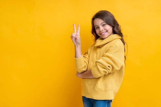 Menina com dois dedos levantados sorrindo Foto gratuita