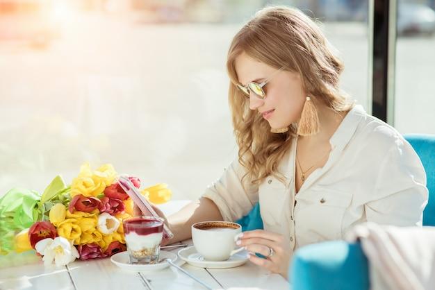Menina com flores, café, iogurte e telefone em um café Foto Premium