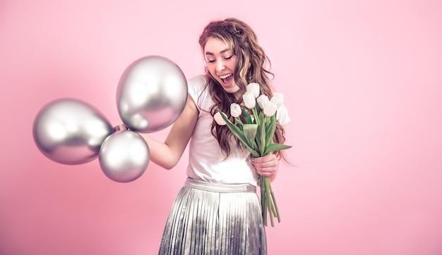 Menina com flores e bolas em uma parede colorida Foto gratuita