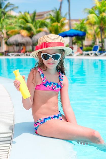 Menina com garrafa de creme de sol sentado na beira da piscina Foto Premium