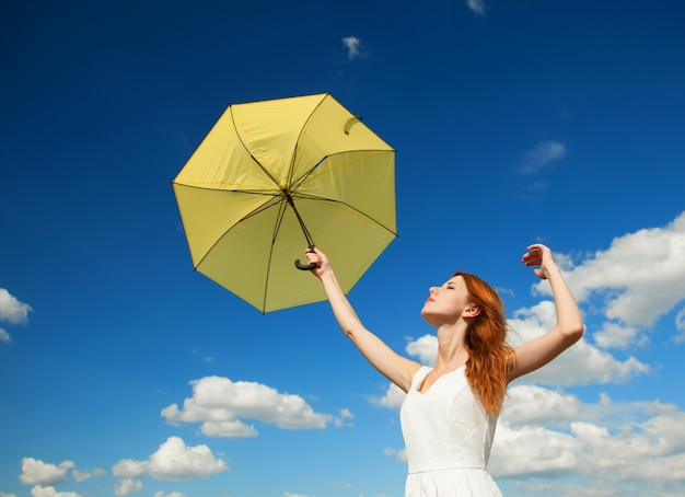 Menina com guarda-chuva no fundo do céu. Foto Premium