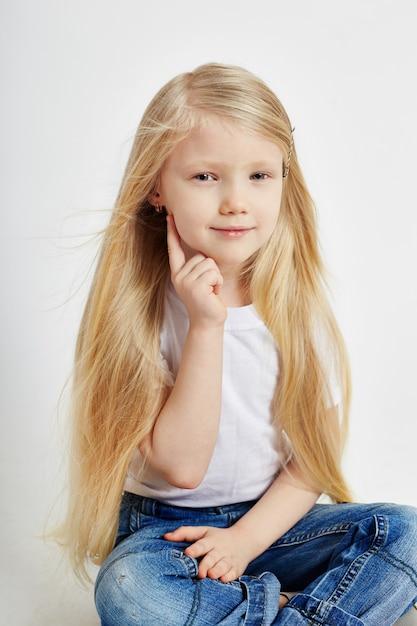 Menina com longos cabelos loiros e jeans Foto Premium