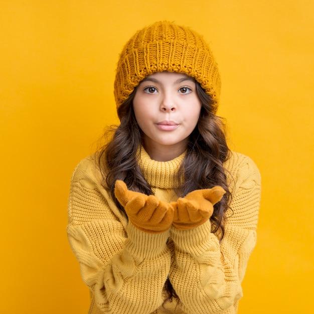 Menina com luvas e chapéu de inverno mandando um beijo Foto gratuita