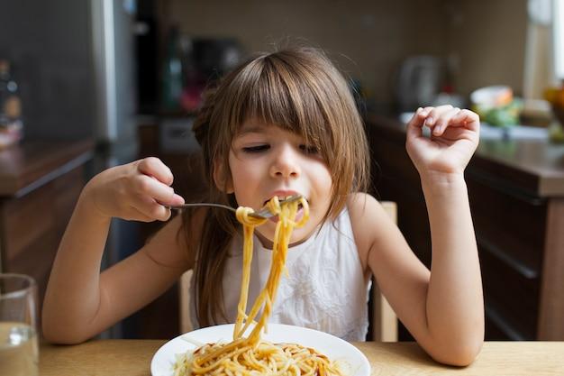 Menina com macarrão prato interior Foto gratuita