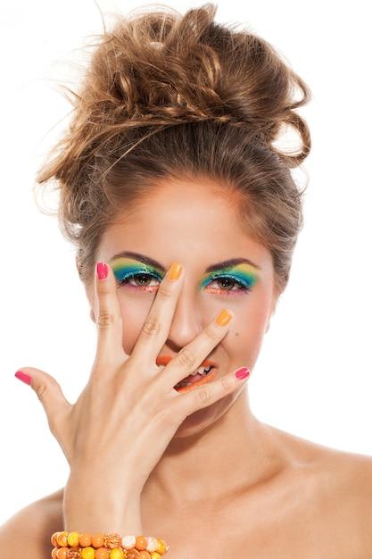 Menina com manicure colorido e maquiagem Foto gratuita