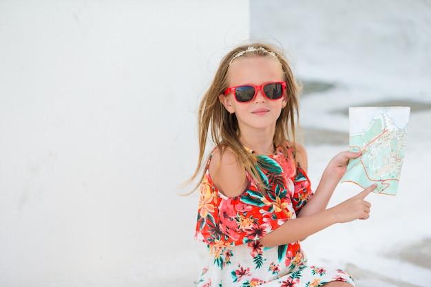 Menina com mapa da ilha ao ar livre em ruas antigas um mykonos. garoto na rua da típica vila tradicional grega, com paredes brancas e portas coloridas na ilha de mykonos, na grécia Foto Premium