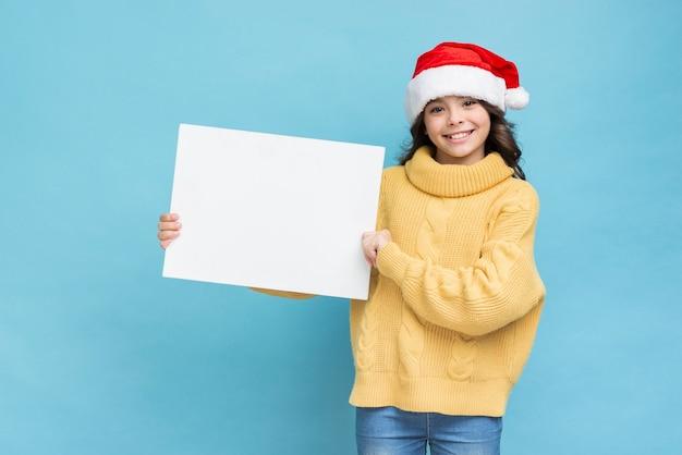 Menina com maquete de pôster nas mãos Foto gratuita