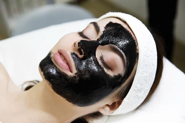 Menina com máscara preta encontra-se na mesa no salão de spa Foto gratuita