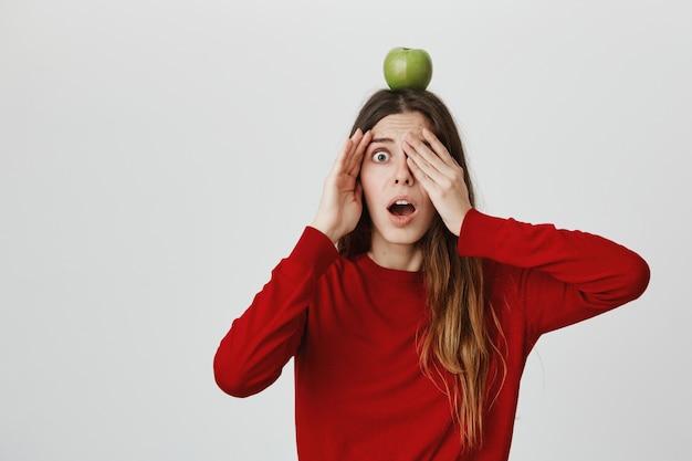 Menina com medo de abrir os olhos e soltar a mandíbula preocupada como alguém atirando flecha no alvo da maçã na cabeça dela Foto gratuita