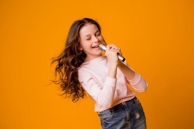 Menina com microfone sorrindo cantando Foto Premium