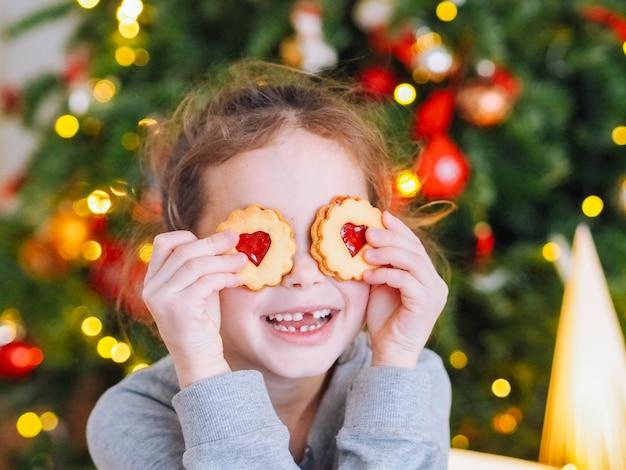 Menina com mudança de dentes fazendo biscoitos de natal e brincar debaixo da árvore de natal na sala com luzes de natal Foto Premium