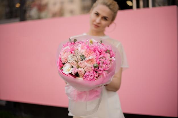 Menina com o buquê de flores cor de rosa Foto Premium
