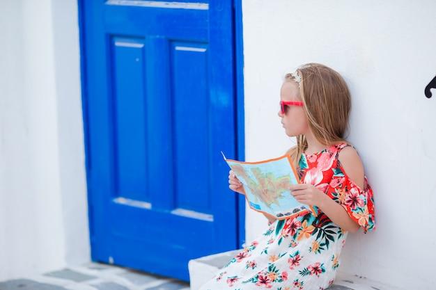 Menina com o mapa da ilha ao ar livre em ruas velhas um mykonos. Foto Premium