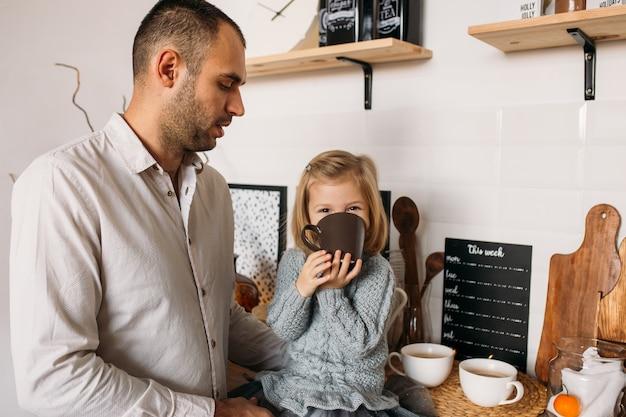 Menina com o pai na cozinha em casa. menina bonita está sentado na cozinha com uma xícara de chá. Foto Premium