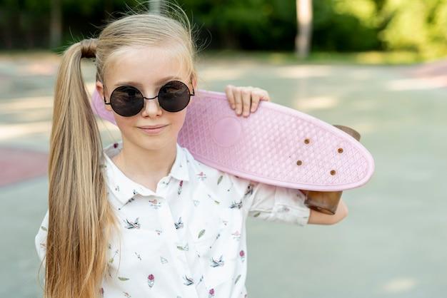 Menina com óculos de sol e skate cor de rosa Foto gratuita